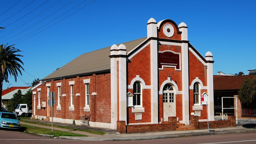 A large red brick building with ornate cream features stands on a corner with bright blue sky above