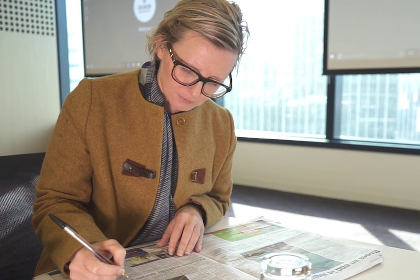 A woman sits at a table, marking a newspaper with notes.