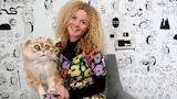 A blonde curly-haired blue-eyed woman holds a large ginger puppet cat, in story about puppetry helping dementia patients.