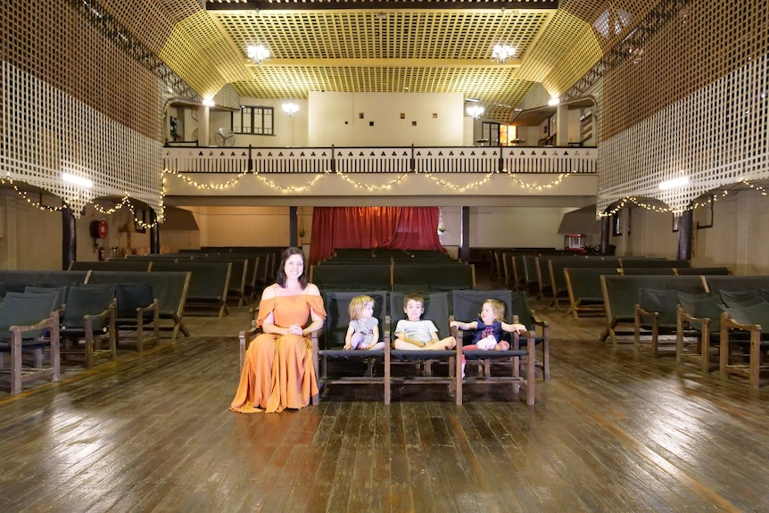 A woman and her three children sit in the wooden front row seats of an old theatre
