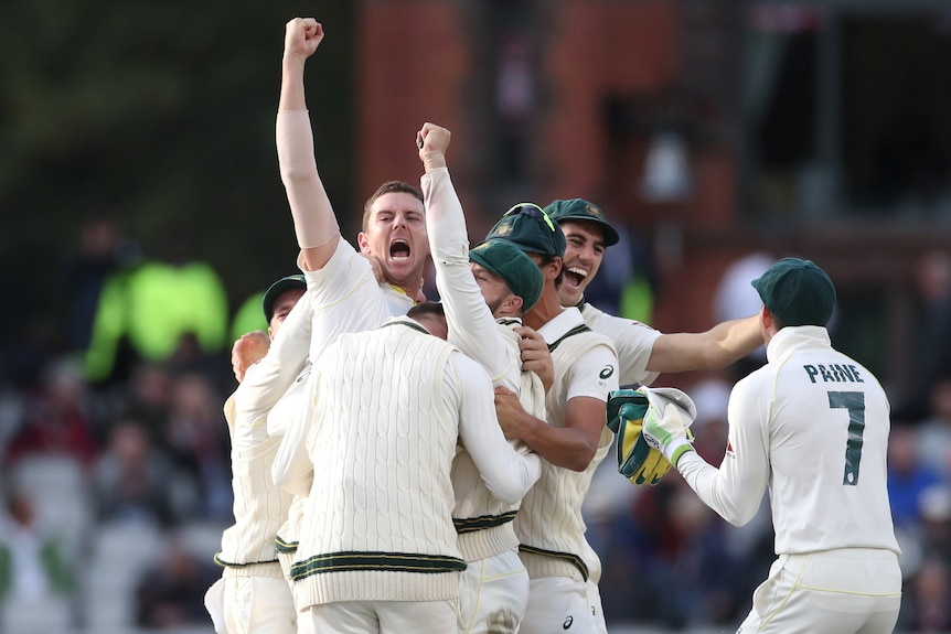 A group of cricketers hug as the man who took the winning wicket thrusts his fist to the sky.