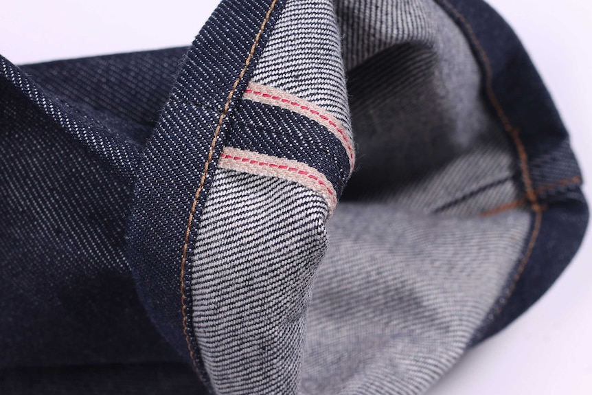 A pair of blue jeans with the cuff upturned, showing two red lines on the inseam, an example of a men's casual wardrobe staple