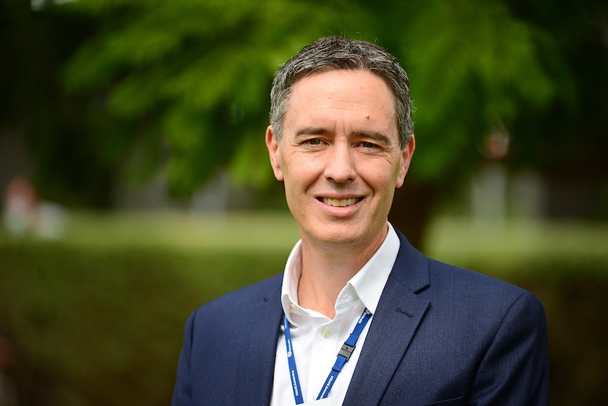 A man in a suit standing in a park and smiling.