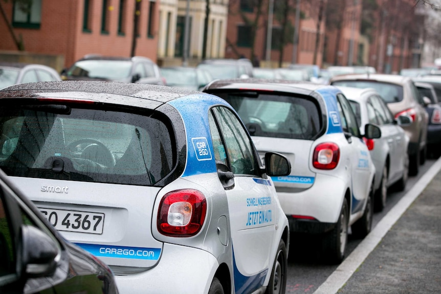 Two small cars with 'Car2Go' branding sit parked in a line of cars on the right hand side of a Berlin street.