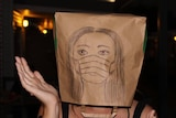 A person with a paper bag on their head with a self-portrait.