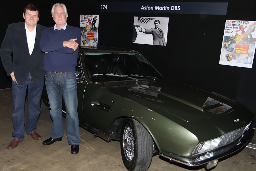 Two men stand next to an olive green sports car