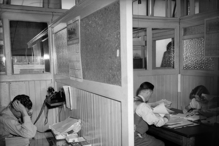 Black and white shot of people working at wooden desks in wood and glass cubicles