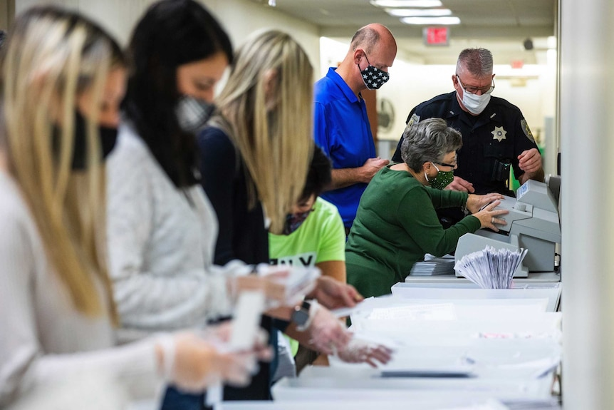 Election workers prepare ballots for counting.