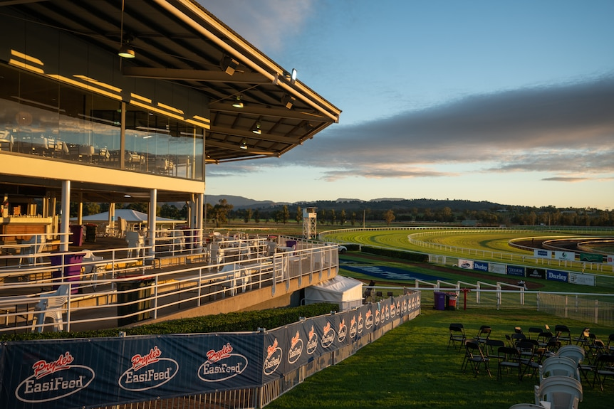 A racing club's stands and corporate box at sunrise. Track is in the background and empty chairs are in foreground
