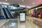 Near-empty mall and sign of coronavirus information at Westfield Garden City shopping centre in Brisbane.