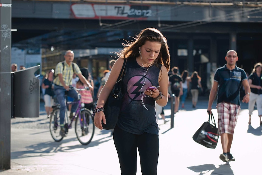 A female pedestrian texts on her phone as she crosses the road.