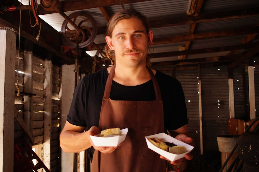 """WA chef Paul Iskov holding two """"street food""""-style meals he has created using native foods."""