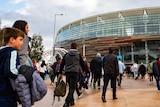 A crowd walks towards Perth Stadium.