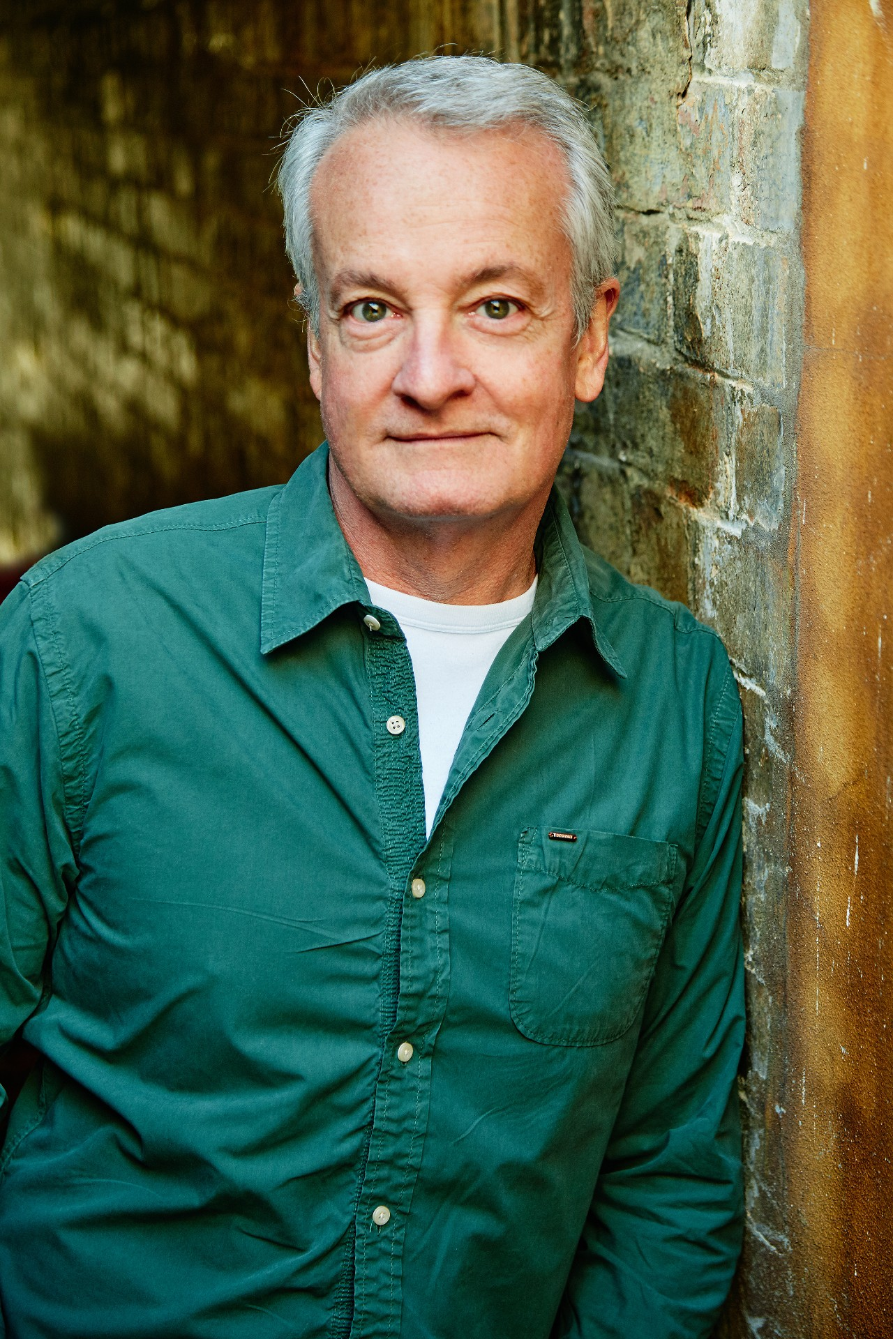 A 60-something man looks into the camera. He's leaning against a brick wall, while wearing a dark green button-up shirt