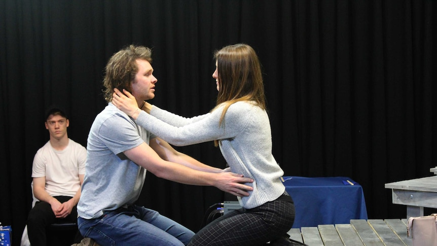 Two actors kneeling on stage with their arms around each other.