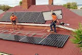 A workman carries a solar panel on a rooftop.