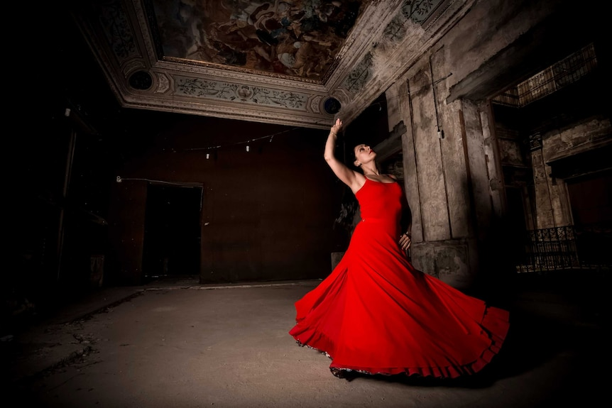 A woman holds up one arm as she spins in a red dress.