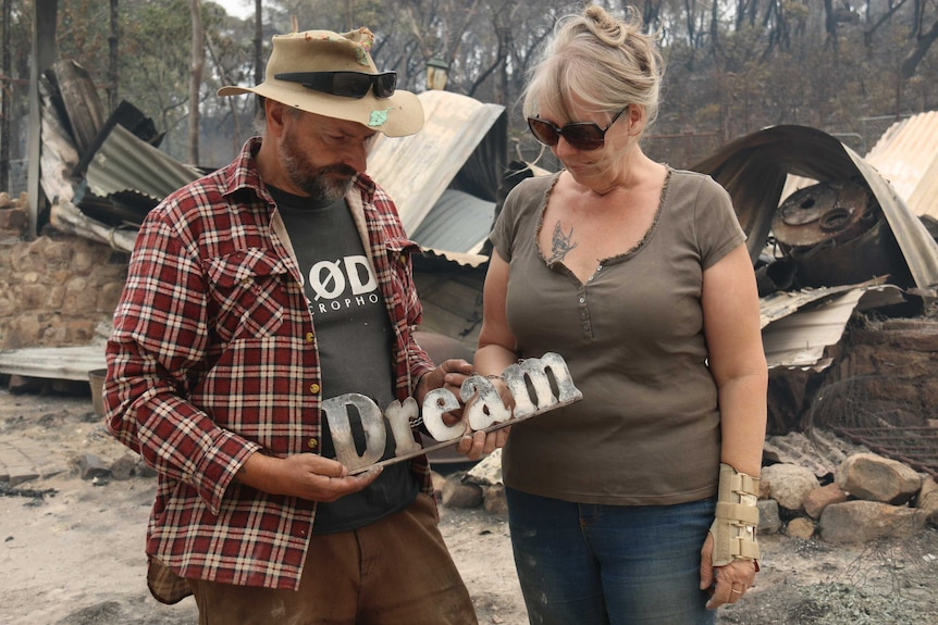 A couple stands in front of a destroyed home, holding a sign that says dream