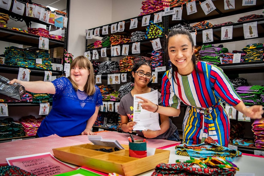 Sophie Grivas and Amrita Ramjas and Stephanie Trinh-Tran laugh and reach their arms out while holding fashion products.