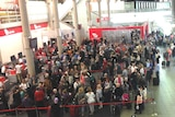 An aerial shot shows long lines of passengers and a makeshift tent where bags were being searched.