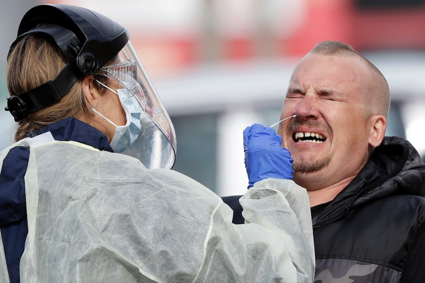 A man grimacing while a health worker in PPE sticks a swab up his nose
