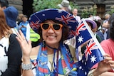"""Jamie """"from Sydney"""" grins, wearing an Australian flag hat and holding a small flag."""