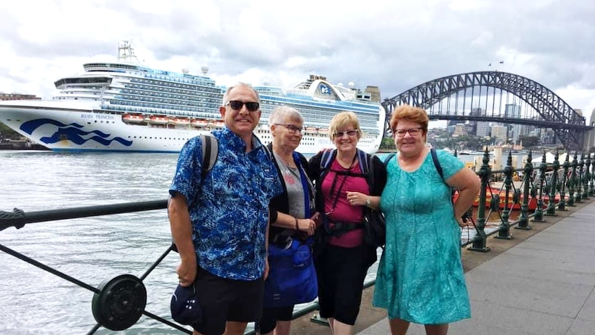 A group of people smiling and happy in the harbour with a cruise ship in the background.