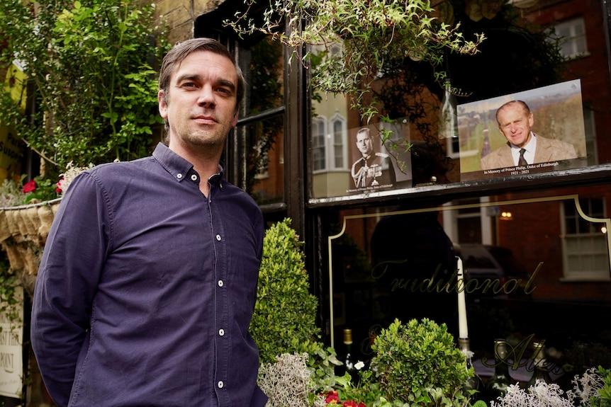 Ein Mann in einem blauen Hemd steht neben einem Kneipenfenster mit Porträts von Prinz Philip.
