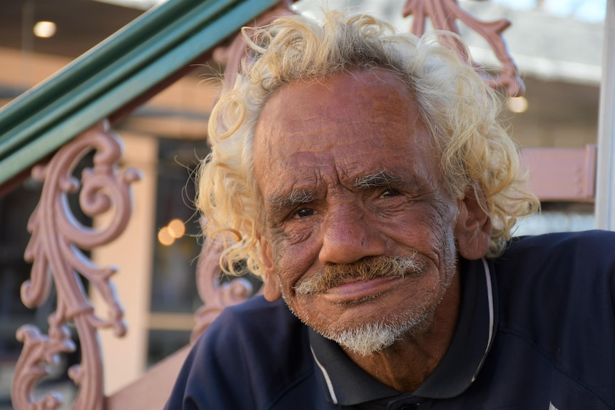 A Aboriginal man with curly blonde hair smiles at the camera.