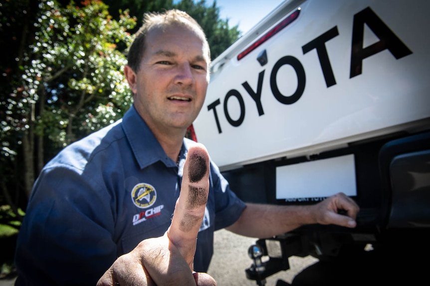 Diesel mechanic Andrew Leimroth with black soot on his finger from the exhaust tailpipe of a Toyota Hilux