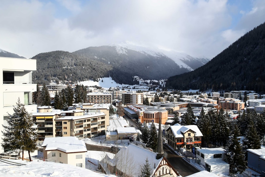 A town with a few apartment buildings set among snow-capped mountains.