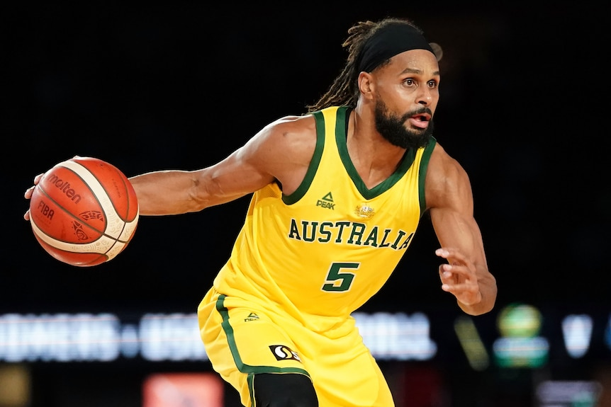 An Australian male basketballer dribbles the ball with his right hand.
