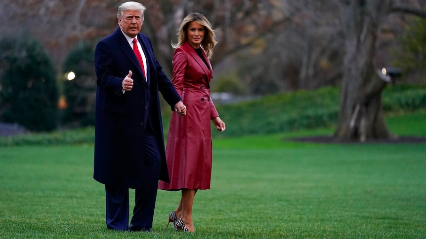 Donald Trump and Melania Trump holding hands while standing on a grass lawn. She is in a red coat.