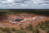 An aerial shot of a drilling site in the Beetaloo Basin. Machinery and vehicles are in a land clearing surrounded by trees,