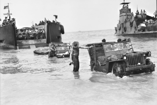 Black and white image of Australian War Memorial landing craft delivering jeeps and troops ashore during World War II