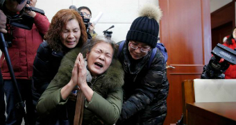 Wang Yulian is held up by two women as she holds her hands in a prayer position with photographers behind them.
