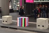 A series of large concrete blocks outside a busy railway station, one covered in stripy colourful material.