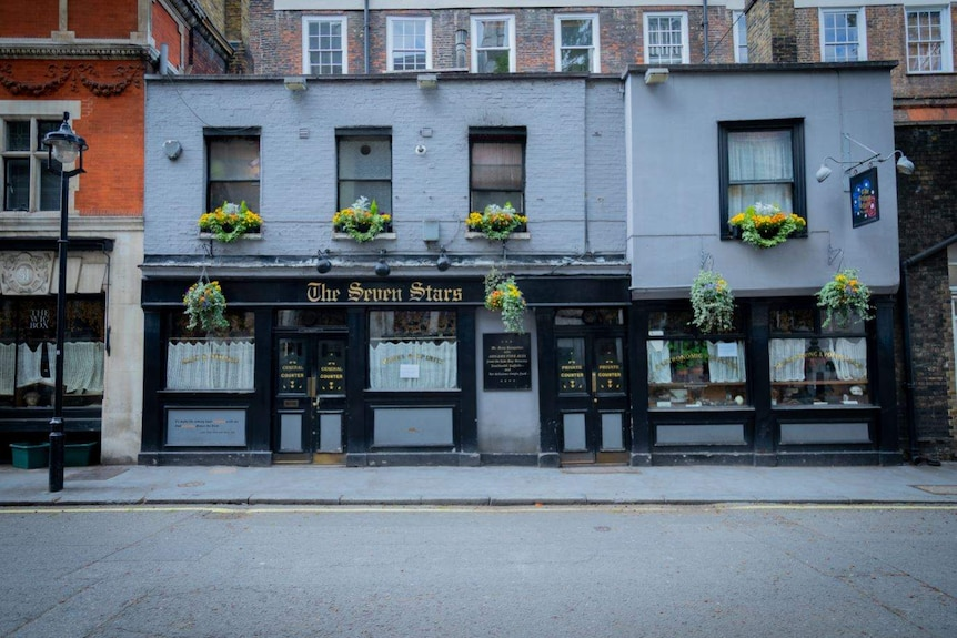The exterior of the Seven Stars pub with hanging floral baskets in the windows