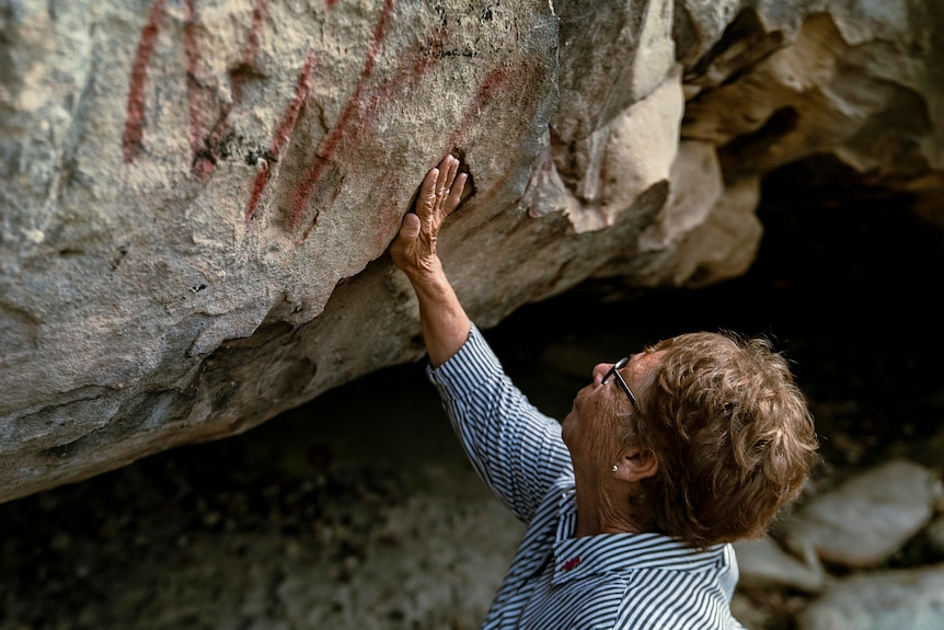 Aboriginal elder Aunty Barbara Simms places her hand in a crevice high up on a cave wall.