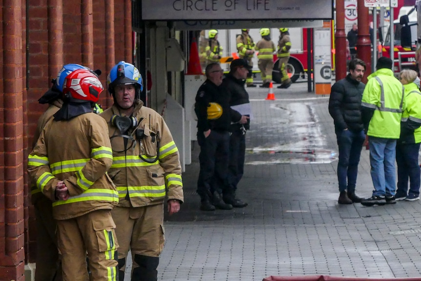Two firemen standing on the street.