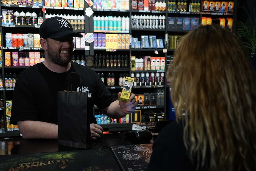 A shopkeeper sells a vaping product to a woman.