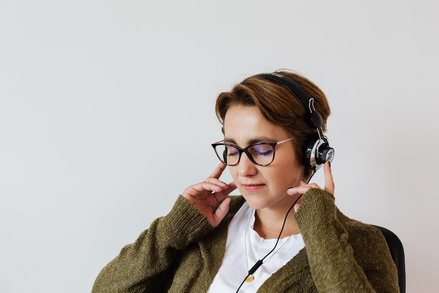 A person with short hair is seen wearing a khaki cardigan while holding their hands over their headphones, eyes closed