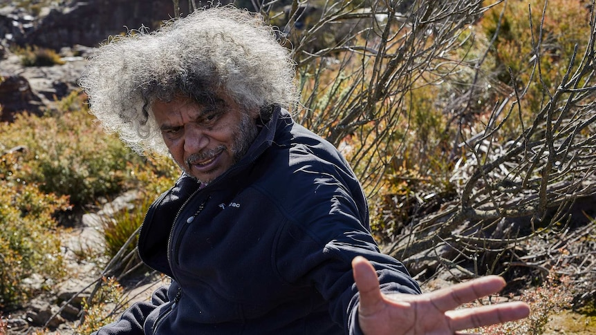 An Indigenous man points in the bush