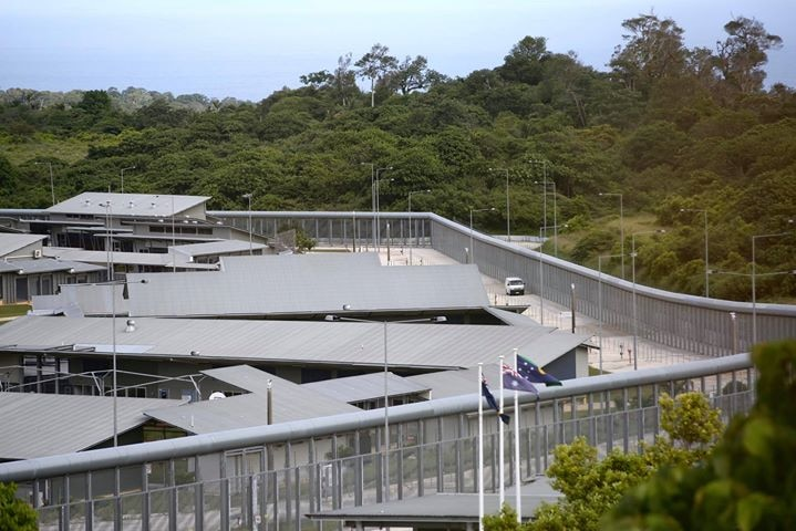 A complex with a high security fence and satellite dishes and flags.