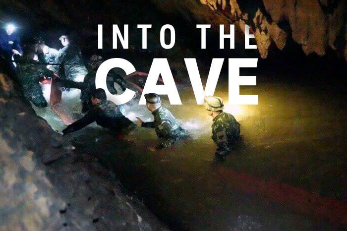 A group of rescuers travel into the cave. The words 'Into the cave' are transposed into the image.