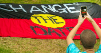 "A man takes a photo of an Indigenous flag with ""change the date"" written on it."