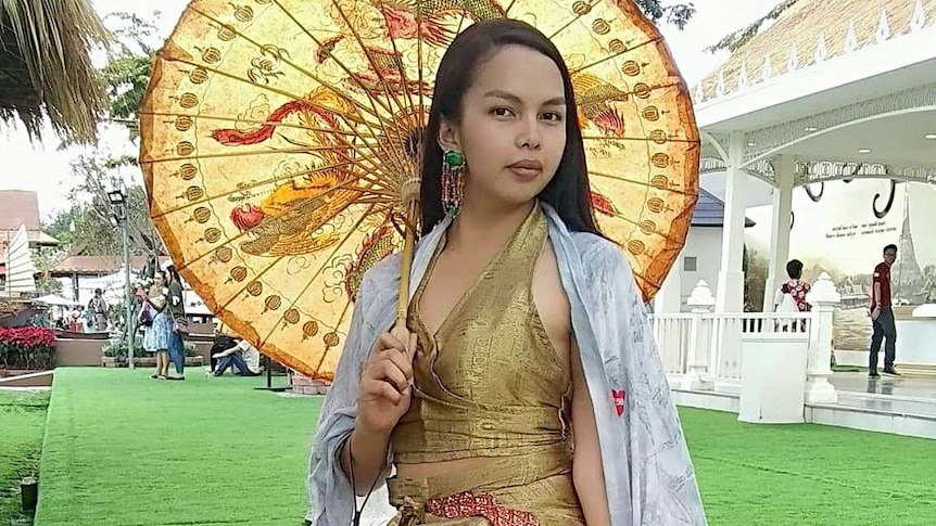 A well-dressed woman sits holding an umbrella.