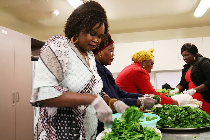 Monica Majak (left) and volunteers from the South Sudanese Mothers Coalition prepare lettuce for kombo, a traditional dish.
