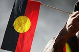 An elder holds an Aboriginal flag