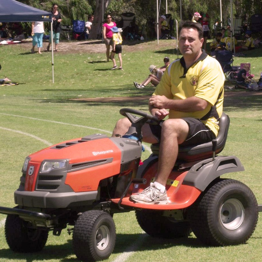 Bradley Robert Edwards sits on a red ride-on lawnmower on a grass oval in a yellow shirt.